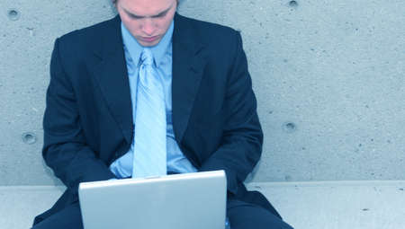 Business man with blue suit, blue shirt, and blue tie is sitting up against a concrete wall typing on his laptop Stock Photo - 807606