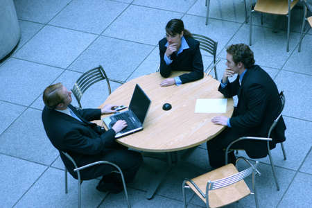 two men and woman are sitting around a table discussing business matters with a laptop on the table