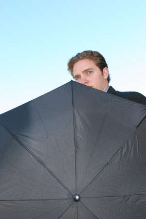 Businessman is holding umbrella with only his face showing Stok Fotoğraf