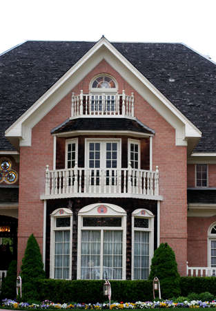 Colonial home with red brick, white trim, and black shingles\ with beautiful front garden