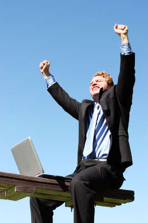 Businessman in black suit and blue shirt and tie is lifting his arms up in celebration as he sits on the bench next to his laptop