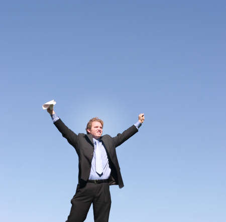 resourcefulness: Businessman wearing black suit, blue shirt, and blue tie holds arms out in celebration as he holds onto a piece of paper in his hands