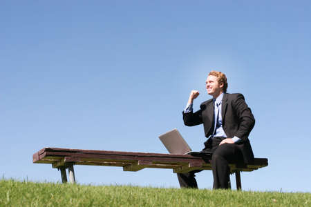 Business man in black suit and blue shirt and tie is holding one arm up in celebration, as he sits on a park bench, next to his laptop Stock Photo