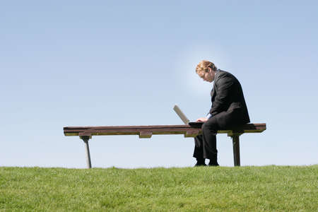 Businessman in black suit and tie is looking down at his laptop, which is on a park bench