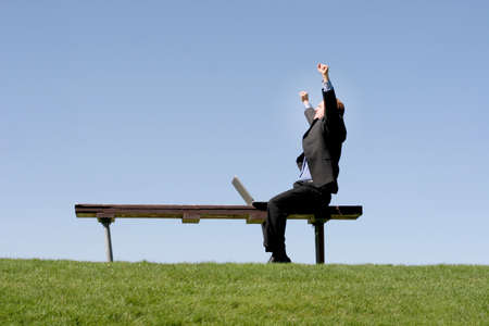 Businessman is waving his hands in celebration as he sits on a park bench, next to his laptop Banque d'images
