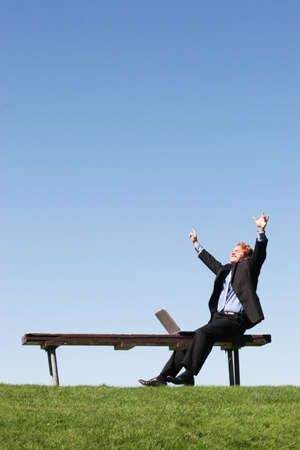 Business man raises arms in triumphant victory as he sits on a park bench, next to his laptop against the blue sky and green grass Stock Photo