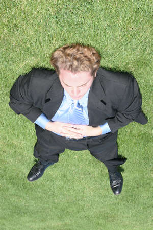 Businessman wearing black suit and blue shirt is completely sprawled out on the green grass