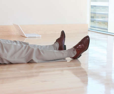 lies down: Legs of businessman as he lies down on the wooden floor, next to his white laptop