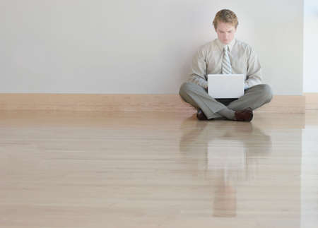 Businessman in tan shirt and tie is typing on his white laptop on wooden floors