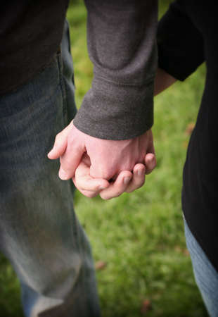resourcefulness: Couple holding hands wearing jeans in the green grass