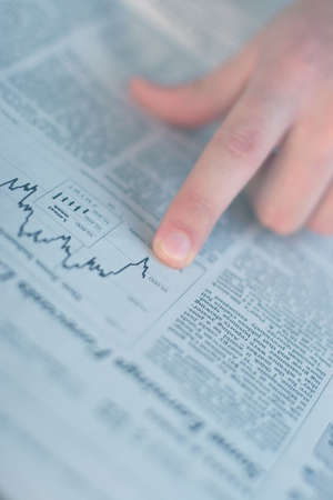 Finger pointing to the chart in the business section of the newspaper