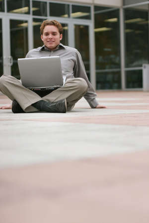 Businessman wearing gray shirt has his hands planted on the ground as he looks down at his laptop Zdjęcie Seryjne