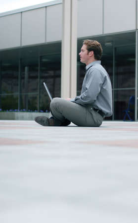 back straight: Businessman with laptop sits in the middle of the business plaza with his back straight