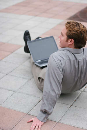 Businessman in relaxed position sits in the middle of the plaza with his laptop on his lap Stock Photo - 807667