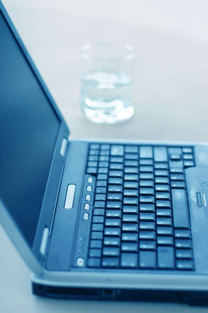 Gray laptop on table next to a glass of water