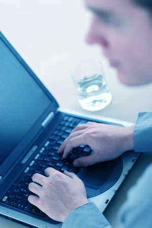Businessman looks off as his hands type on his laptop and with a glass of water on the table