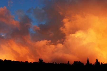 generosidad: El sol est� fijando y sus rayos de sol se reflejan en nubes anaranjadas con un horizonte oscuro Foto de archivo