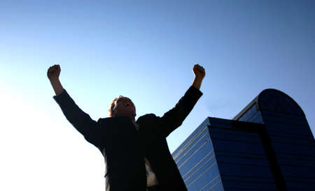 Busines man holding up his arms in victory with a blue office building in the background Stock Photo