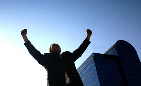 spunk: Hombre de negocios que sostienen sus brazos en la victoria azul con un edificio de oficinas en el fondo  Foto de archivo