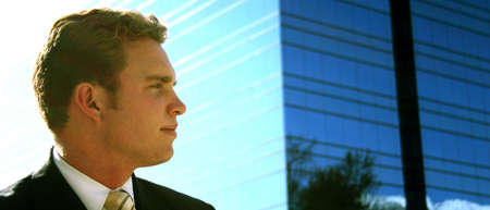 Businessman in black suit, white shirt, and tan tie looks off with a blue window building in the background Imagens