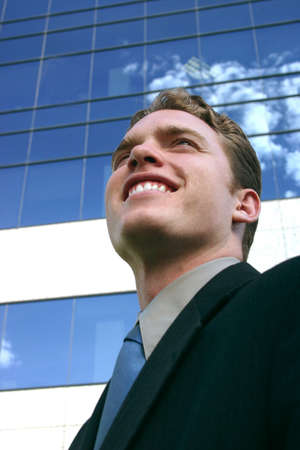 spunk: Business Man looking up standing in front of a business building