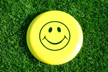 Happy Face Frisbee is on a green bed of grass in the summer