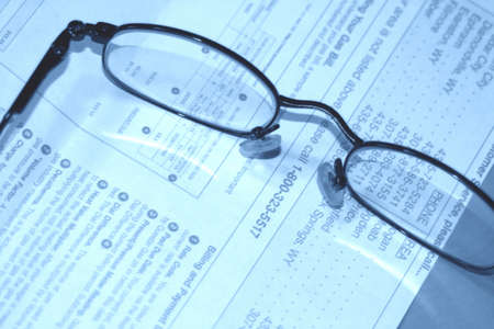 economic issues: Eyeglasses rest on a bill on the table Stock Photo