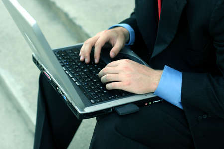 Business man in black suit, blue shirt, and red tie is busily typing on laptop on courthouse steps Stock Photo - 456670