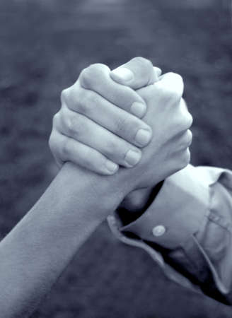 resourcefulness: Hand of woman and hand of man is clasped together in symbolic strength of unity