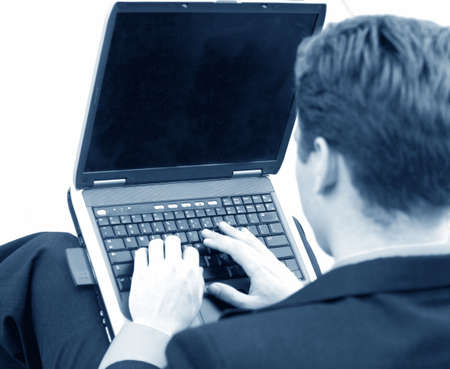 black and white shot of businessman typing on his laptop