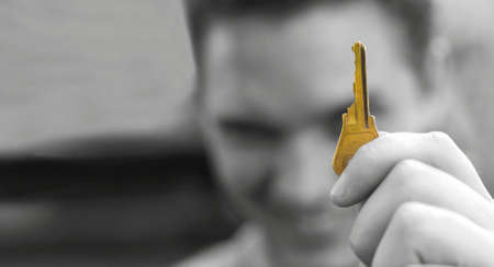 Young man smiles in the background as he holds in his hand the very golden key to success Stock Photo