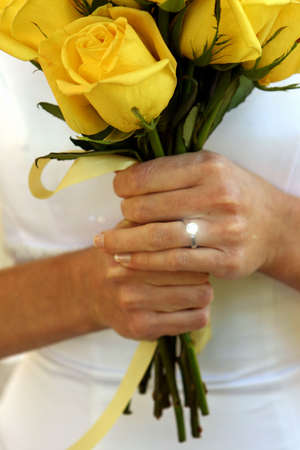 Bride holds boquet of yellow roses as her diamond ring sparkles Stock Photo - 456624