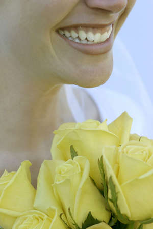 hitched: Beautiful bride gives big smile as she holds a bouquet of yellow roses