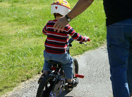 helps: Father helps son ride his new bike