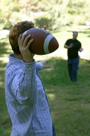 younger: Two younger men throw the football around outside in a green field