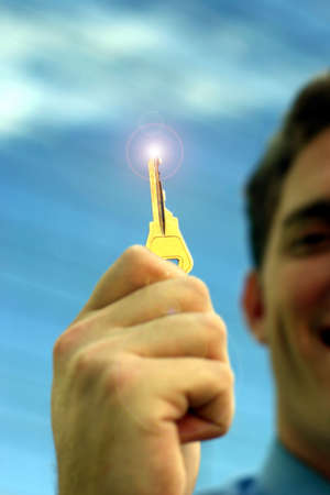 Business man is holding up golden key with a light that is shining at the tip of the key