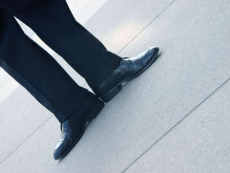 spunk: Business man has his feet pointed out in opposite directions on the concrete floor