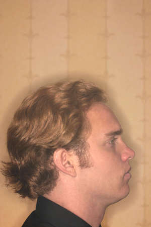 Profile shot of young man with hair like the mane of a  lion