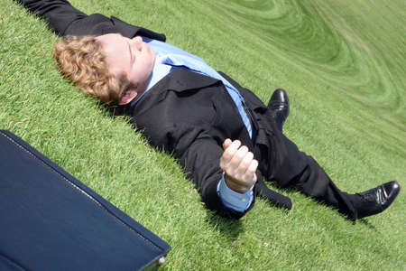 race for time: Business man has finally had it, collapses into relaxation on the green hill of tranquility