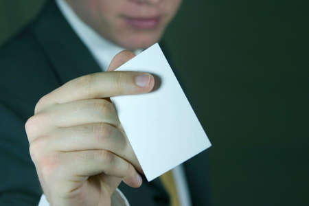 Business man in dark suit holds out blank business card