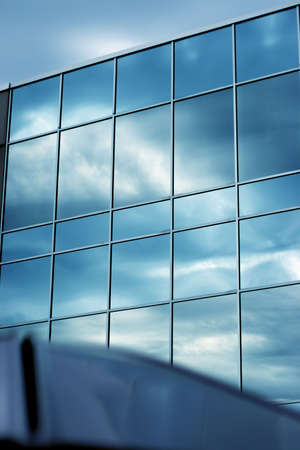 figuration: Business office building with large blue windows against blue sky