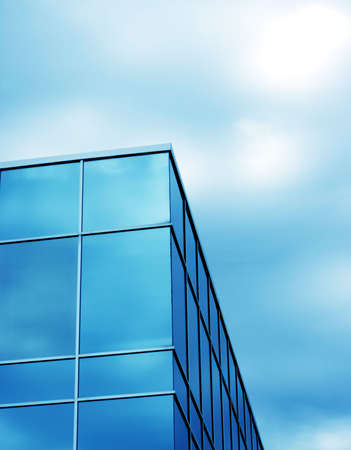 Glass business building with blue windows against blue sky Imagens