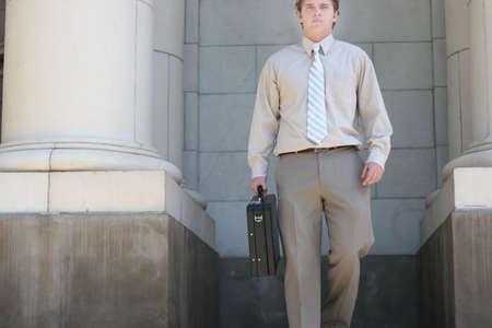black briefcase: Abogado es caminar por los pasos de la corte hacia usted con un malet�n negro en su mano