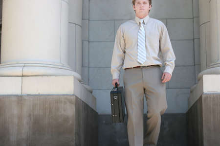 Lawyer is walking down the steps of the courthouse towards you with a black briefcase in his hand photo
