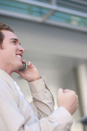 Younger businessman in tan shirt is exicted to talking on his cell phone against office building photo