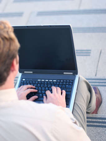 Business man in tan shirt is busily typing on laptop as he sits on his steps