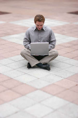 Businessman wearing gray shirt is holding laptop in his lap as he sits in the middle of a business building plaza Stock Photo