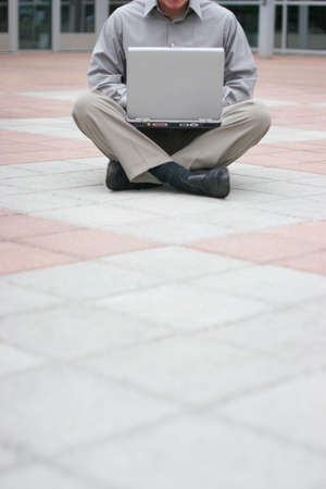 Businessman wearing a gray shirt is sitting cross-legged in the middle of a business building's plaza with a laptop squarely in his lap Imagens - 460456