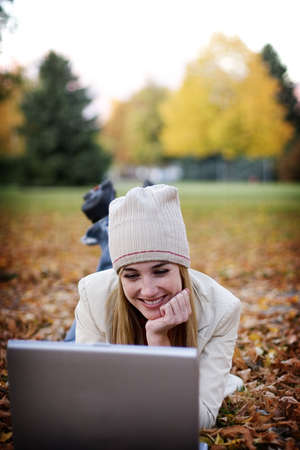 Woman with laptop relaxes in the fallen autumn leaves as she taps on her laptop Stock Photo