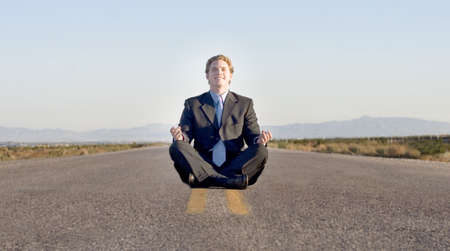 inventiveness: Business man in black suit and blue shirt is meditating on the road to success  Stock Photo
